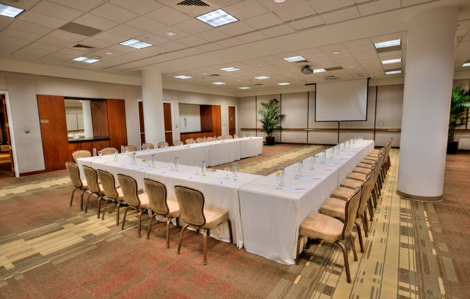 U-shaped meeting table facing screen in Beverly Hilton Whittier Room