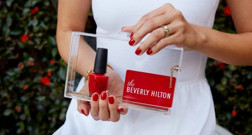 Freshly manicured hands holding red nail polish and gift card