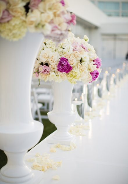 White and pink floral centerpieces line the aisle in an outdoor ceremony