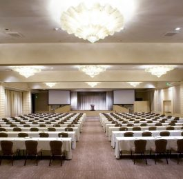 Rows of rectangular tables face a podium and two screens for a large function in the Beverly Hills Ballroom