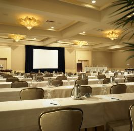 Rows of tables and chairs face a screen in the Wilshire Ballroom